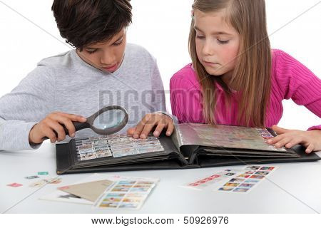 Kids looking at a stamp album