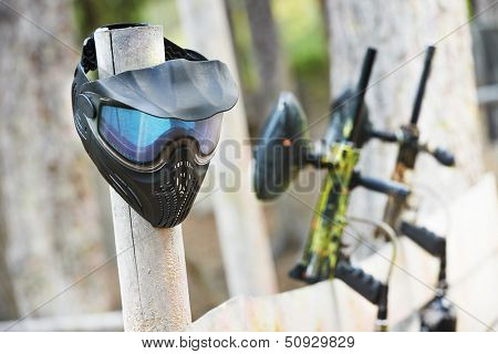 Equipment for paintball playing. Protective mask and gun paintballing marker in forest