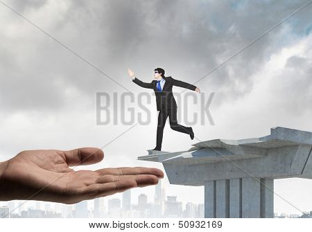 Image of running businessman at the edge of bridge supported by human hand
