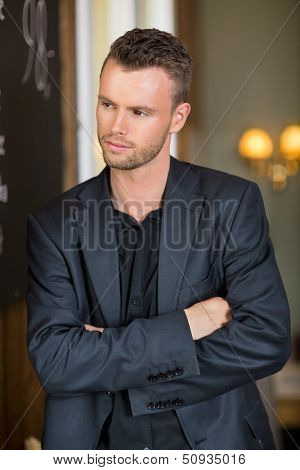 Thoughtful young businessman standing arms crossed in coffeeshop
