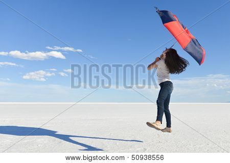 Girl jumps with an umbrella with a vast white salt flats background in Bonneville, Utah