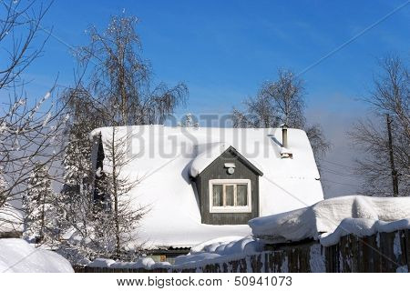 snow-covered roof of a village house on the background of bright blue sky