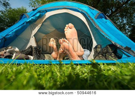 Feet of a young couple lying in a tent