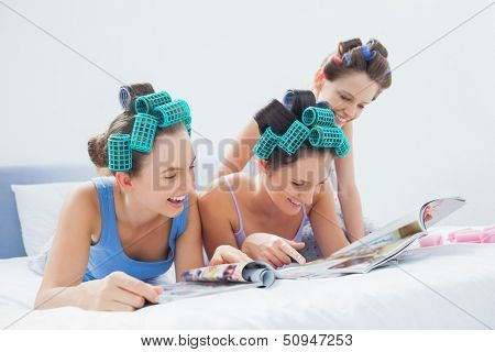 Girls wearing pajamas and hair rollers sitting in bed with magazines at sleepover