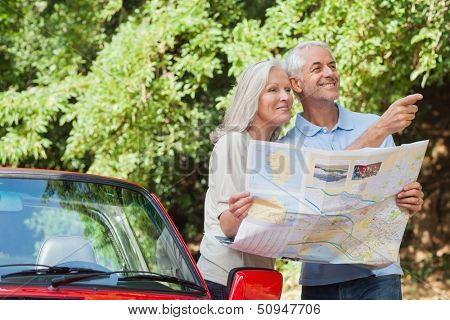 Cheerful mature couple by their cabriolet reading map looking for direction