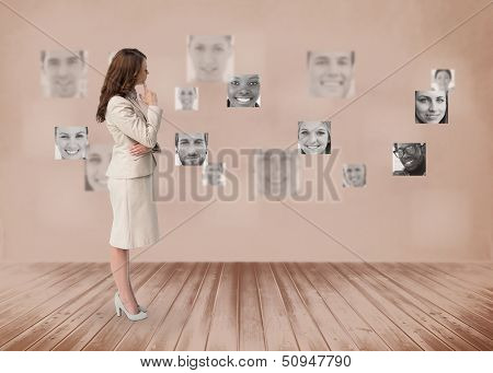 Businesswoman looking at futuristic interface in black and white showing faces