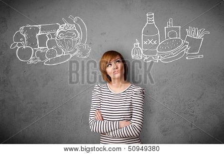 Pretty young woman choosing between healthy and unhealthy foods