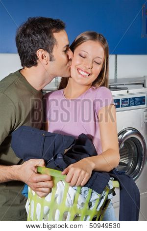Side view of young man kissing woman on cheek with basket of clothes at laundromat