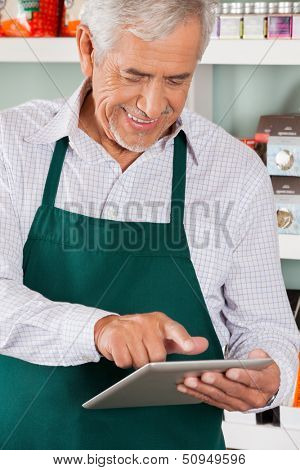 Happy senior male owner using digital tablet in grocery store