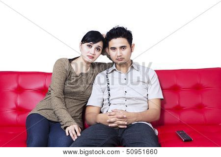 Unhappy Couple Watching Tv And Sitting On Red Sofa