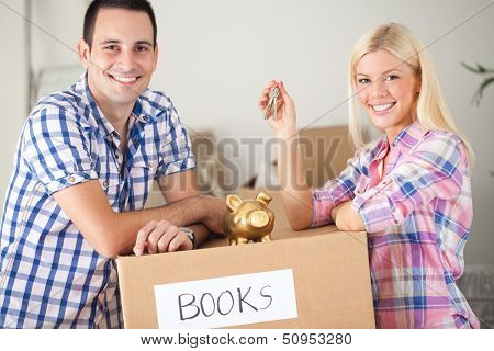couple with piggy bank and keys with moving boxes, concept saving