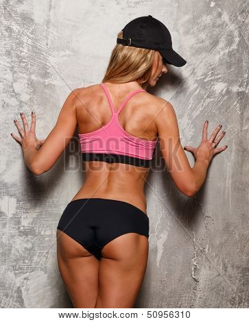 Sporty woman in pink top with beautiful beautiful body against concrete wall