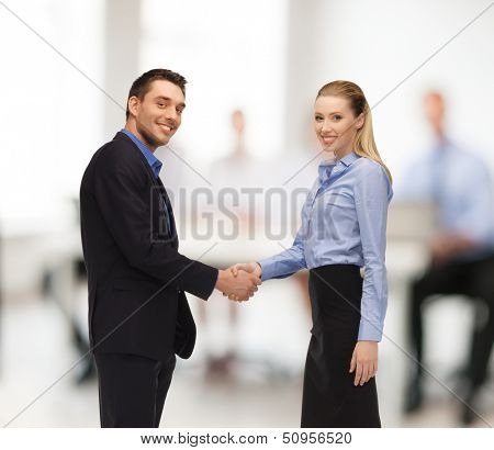 office, buisness, teamwork concept - man and woman shaking their hands