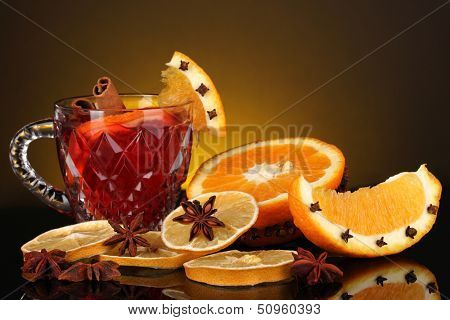 Fragrant mulled wine in glass with spices and oranges around on yellow background