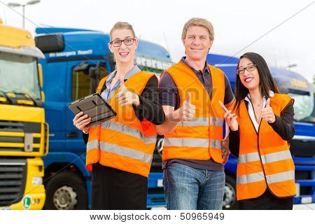 Logistics - proud driver or forwarder and colleagues with tablet computer, in front of trucks and trailers, on a transshipment point, its a good and successful team