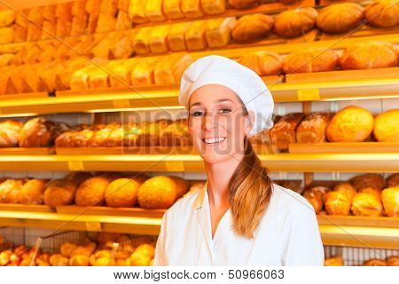 Female baker or saleswoman in her bakery selling fresh bread, pastries and bakery products