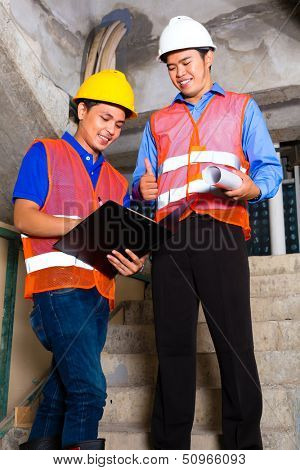 Chinese supervisor or controller and worker or architect look on building site on a clipboard
