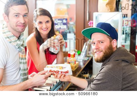 Hotdog - young customers in a snack bar eating delicious fast food sausages