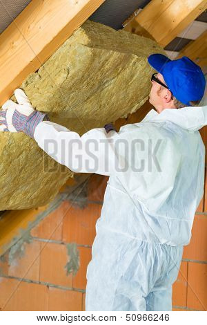 Worker in overall is setting thermal insulating material with gloves in the roof