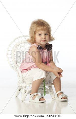 Little Girl In Pink Sitting In Chair