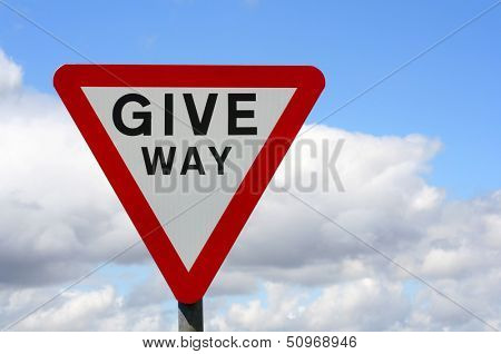 Horizontal photograph of UK Give Way sign with cloudy sky
