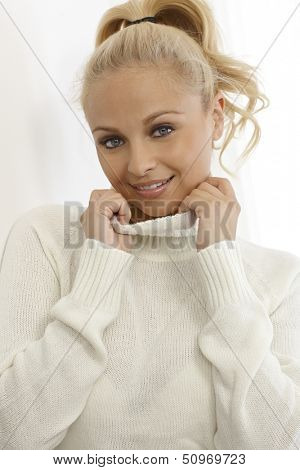Young blonde woman smiling in white turtleneck pullover, having pigtail.