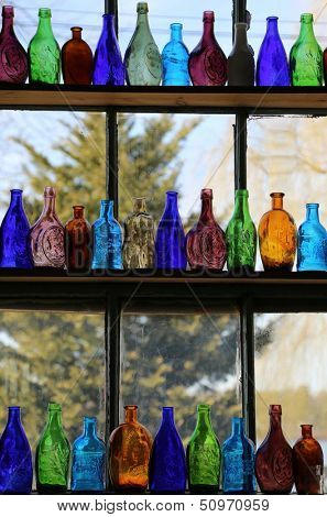 Colorful glass bottles on windowsill