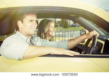 Two young smiling people in a yellow car
