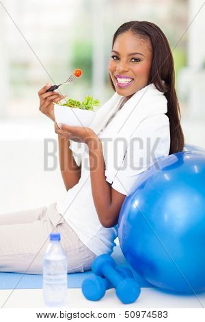 happy african american woman having green salad after working out