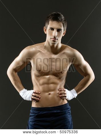 Half-length portrait of half-naked boxer with hands on hips, isolated on black
