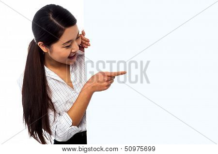 Saleswoman Pointing Towards Ad On Billboard