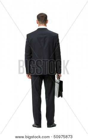 Full-length backview portrait of businessman with case, isolated on white. Concept of leadership and success