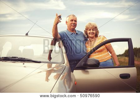Two happy smiling elderly people in car with keys