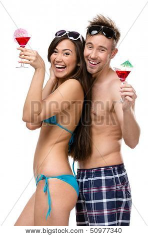Half-length portrait of half-naked couple with cocktails, isolated. Concept of romantic vacations and lovely honeymoon