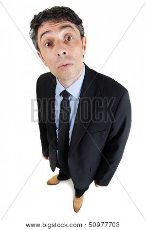 Fun high angle portrait of a middle-aged businessman with a wide eyed inquiring expression or a look of supercilious mockery standing looking up at the camera, isolated on white