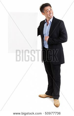 Fun portrait of a smiling businessman with a wide toothy grin holding a blank white sign in his hand with copyspace as he endorses your text or advertisement, isolated on white