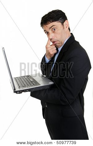 Middle-aged businessman standing sideways handholding his laptop computer gesturing with his finger to his nose in rude derision or because he is picking his nostril, isolated on white