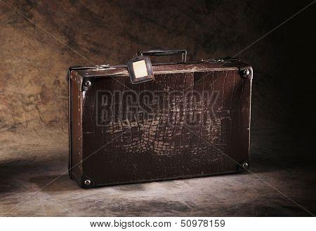 Old brown cardboard suitcase on brown rustic background.