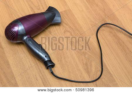 Electric Hair Dryer on wooden floor