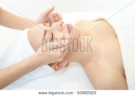 Beautiful young woman receiving facial massage in a spa salon
