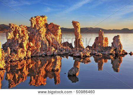 Outliers -  bizarre calcareous tufa formation  reflected in the mirrored surface of the water. A picturesque sunset at Mono Lake. Yosemite National Park, USA