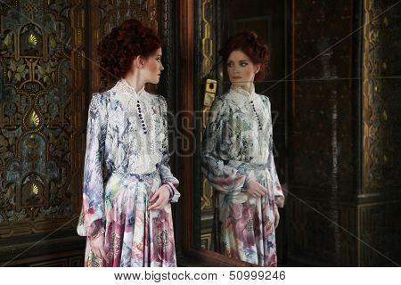 Young beautiful woman standing in the palace room with mirror.