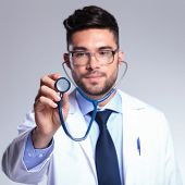 stock photo of rutin  - young male doctor listening and looking at the stethoscope - JPG