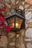 stock photo of light fixture  - Dark brown outside lighting fixture against a stone wall - JPG