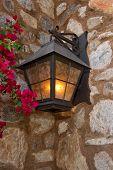 foto of light fixture  - Dark brown outside lighting fixture against a stone wall - JPG