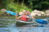 stock photo of down jacket  - Two smiling young women kayaking down a river - JPG