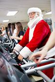 foto of crazy hat  - Santa Claus workout  on a treadmill at gym - JPG