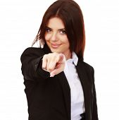Young happy businesswoman pointing at you. Focus on finger