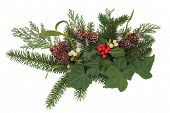Christmas floral arrangement with holly, ivy, mistletoe, pine cones and winter greenery over white b