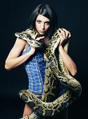 image of pythons  - sexy brunette holding python over black background - JPG